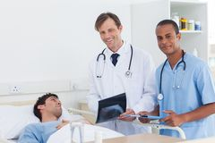 Doctors with radiography standing next to a patient. And looking at the camera Stock Images