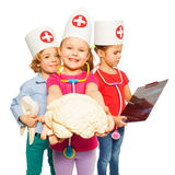 Doctors with x-ray, tooth dummy and cerebrum model. Picture of three little children wearing doctors cap, holding x-ray, tooth dummy and cerebrum model, isolated stock image