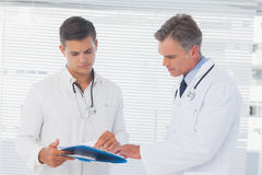 Doctors reading a folder. In a bright office Royalty Free Stock Photo