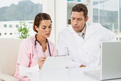 Doctors reading reports while using laptop at medical office Stock Images