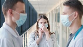Doctors in robes are sharing disposable masks and putting them on faces