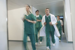 Doctors In Scrubs Running Through Hospital Corridor Royalty Free Stock Photos
