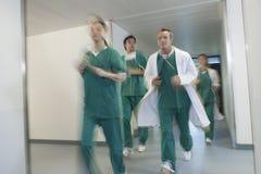 Doctors In Scrubs Running Through Hospital Corridor. Motion blur shot of doctors and nurses in scrubs running through hospital corridor royalty free stock photos