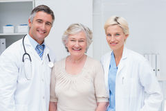 Doctors and senior patient smiling in clinic Royalty Free Stock Photo