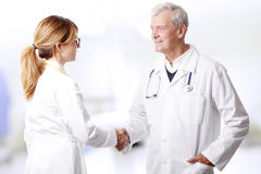 Doctors shaking hands. Portrait of medical team consulting and shaking hands while standing at medical office Stock Image
