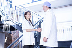 Doctors shaking hands on staircase Royalty Free Stock Photography