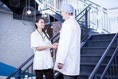 Doctors shaking hands on staircase Royalty Free Stock Photos