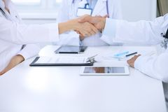 Doctors shaking hands to each other finishing up medical meeting Royalty Free Stock Image