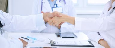 Doctors shaking hands to each other finishing up medical meeting Royalty Free Stock Photos