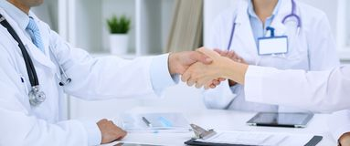 Doctors shaking hands to each other finishing up medical meeting.  Royalty Free Stock Photos
