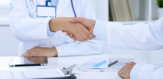 Doctors shaking hands to each other finishing up medical meeting Stock Image