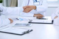 Doctors shaking hands to each other finishing up medical meeting Royalty Free Stock Images