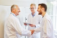 Doctors sharing handschake. As thanks or congratulations gesture stock images