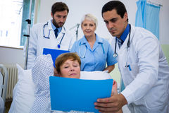 Doctors showing medical report to patient stock images
