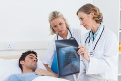 Doctors showing radiography to a patient Royalty Free Stock Photos