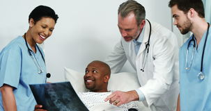 Doctors showing a x-ray report to the patient. Doctors showing a x-ray report to the happy patient in the hospital stock footage