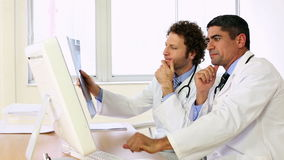 Doctors sitting at desk talking about xray stock video