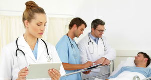 Doctors speaking with sick patient in bed while one uses tablet stock video footage