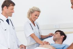 Doctors speaking to a patient. Doctors speaking to a lying patient Royalty Free Stock Images