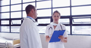 Doctors speaking together while writing notes on clipboard stock footage