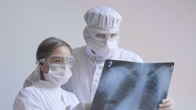 Doctors standing on white background examine x-ray for pneumonia of a Covid-19 patient in the clinic. Coronavirus