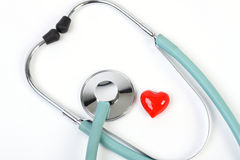 Doctors stethoscope and one small red heart on white background Royalty Free Stock Images