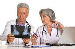 Doctors with stethoscopes looking at x-ray Stock Images