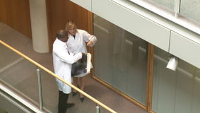 Doctors studying an xray in a hospital. High angle of an AfroAmerican male doctor and beautiful female doctor studying an x-ray in a corridor of a hospital stock footage