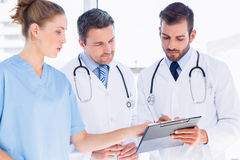 Doctors and surgeon reading medical reports. Two male doctors and female surgeon reading medical reports at the hospital Royalty Free Stock Photography