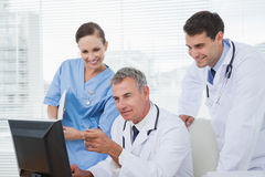 Doctors and surgeon working together on computer Stock Photography