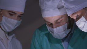 Doctors surgeons operate patient in operating theater. Surgical team performing operation in hospital operating room stock footage