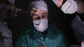 Doctors surgeons operate patient in operating theater. Surgical team performing operation in hospital operating room stock video footage