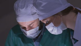 Doctors surgeons operate patient in operating theater, tilt down. Surgical team performing operation in hospital stock video