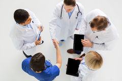 Doctors with tablet pc doing handshake at hospital Stock Photo