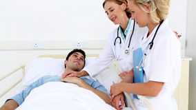 Doctors taking care of a patient stock video