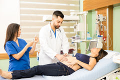 Doctors taking care of pregnant woman. Couple of doctors examining and taking care of a young pregnant women in pain at a hospital Stock Image