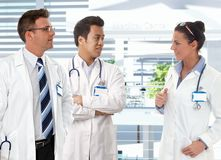 Doctors talking in clinics hallway. Doctors talking in clinics lobby, smiling Royalty Free Stock Image