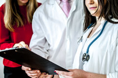 Doctors. Talking about a patient with his documents Stock Photography