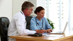 Doctors talking together in front of a laptop. In their office stock video footage