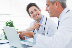 Doctors talking together about something on their laptop Stock Photography