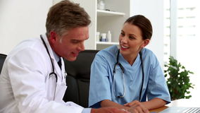 Doctors talking together in their office. Doctors talking together about a patient in their office stock footage