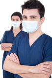 Doctors team. Portrait of a team of doctors, man and woman wearing mask and uniform isolated on white background (selective focus Stock Images