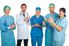 Doctors team applauding. Five different doctors standing in a row and applauding isolated on white background royalty free stock images