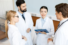 Doctors team discussing diagnosis. Side view of doctors team discussing diagnosis in hospital, caring doctors concept Royalty Free Stock Photos