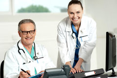 Doctors team. Female assistant typing on keyboard Stock Photography