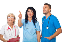 Doctors team looking up. Friendly young doctor woman pointing up to copy space and all team looking there isolated on white background,check also  Medical Stock Photography