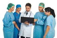 Doctors team using laptop. Hospital director man with laptop showing something to a surgeons team isolated on white background Stock Photo