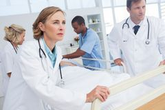 Doctors about to walk with patient bed Royalty Free Stock Image