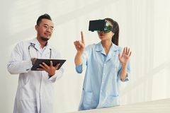 Medical workers exploring virtual reality. Doctors using application on tablet computer to test VR goggles Stock Images