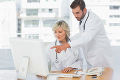 Doctors using computer at medical office Stock Image